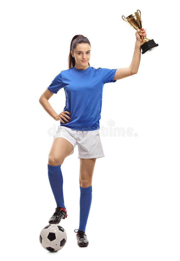 Calciatore femminile con un calcio e un trofeo dorato fotografia stock
