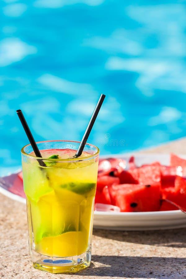 Calcini il cocktail davanti al piatto riempito di melone rosso immagine stock