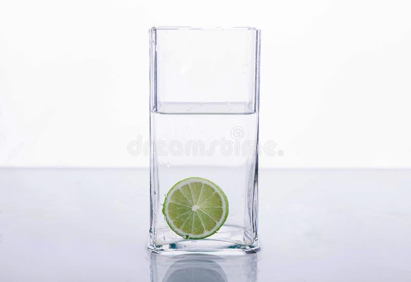 Calcini la spruzzatura in bicchiere d'acqua sul fondo bianco fotografie stock libere da diritti