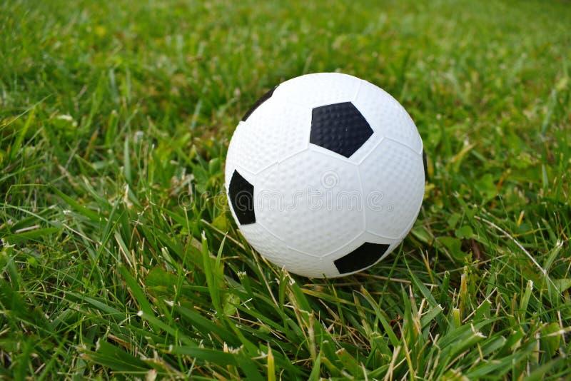 Calcio dei giochi da bambini Il soccerball dei bambini su un'erba verde La vacanza allegra dei bambini di estate immagini stock