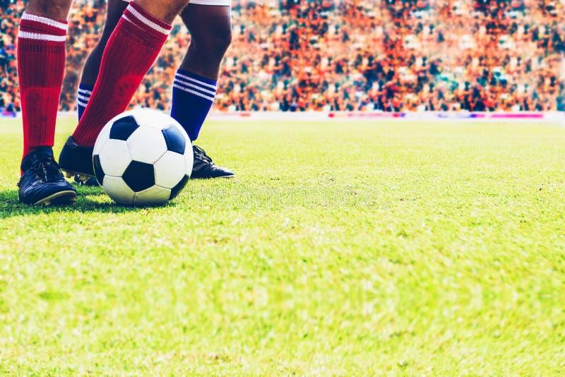 Calcio o giocatore di football americano che sta con la palla sul campo per Ki immagine stock