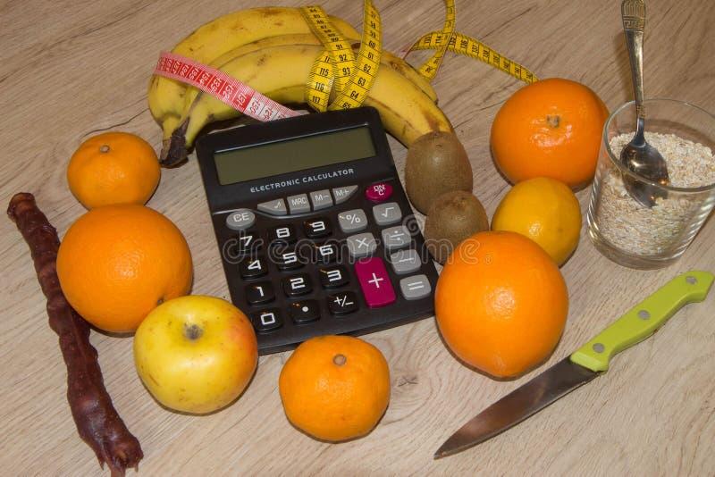 Calcolatore con i cereali, la frutta, la misura di nastro ed il concetto della dieta e dello stile di vita sano fotografia stock libera da diritti