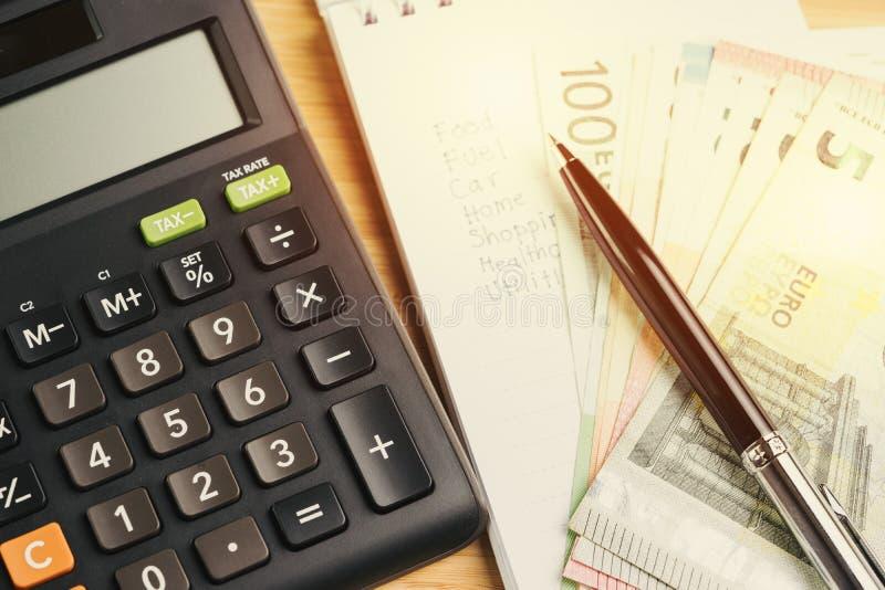 Calcolatore con la penna sulla lista delle spese o sul costo su piccola carta w fotografie stock