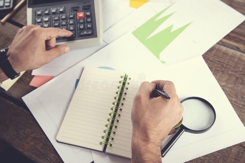 Calcolatore di mano dell'uomo con il blocco note sul documento del grafico immagini stock