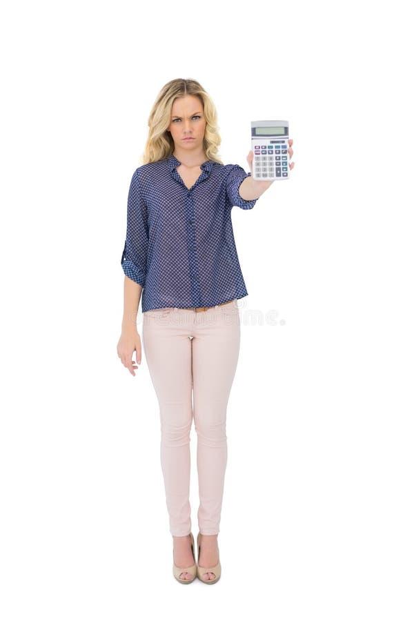 Calcolatore di mostra biondo grazioso aggrottante le sopracciglia fotografia stock