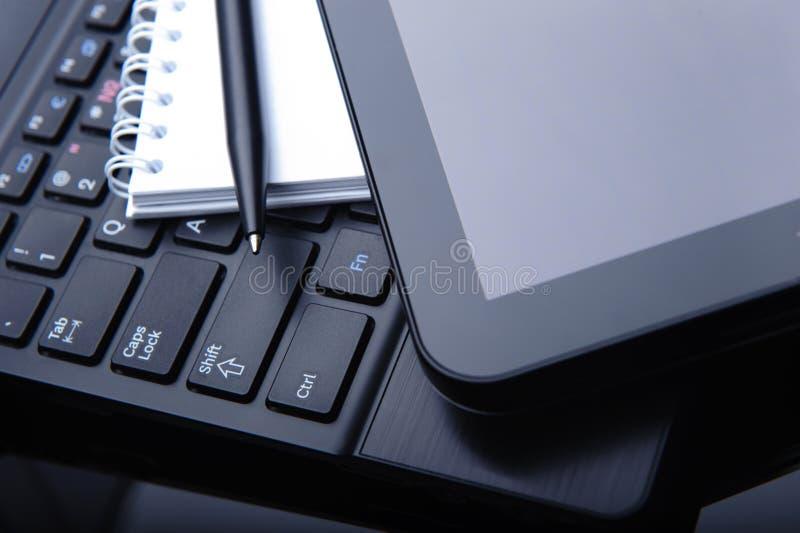 Calcolatore e computer portatile del ridurre in pani sullo scrittorio fotografia stock libera da diritti