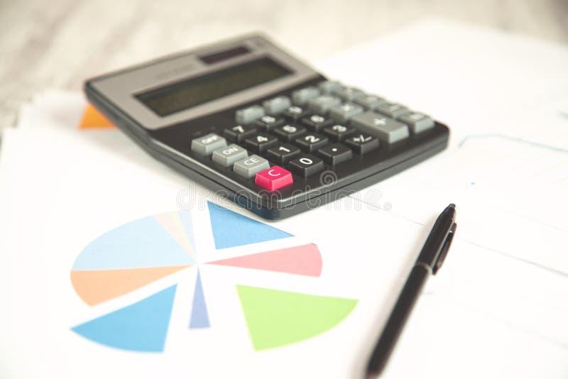 Calcolatore e penna sul grafico fotografia stock