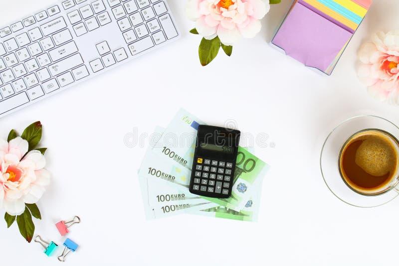 Calcolatore, euro banconote, taccuino in bianco su un desktop bianco accanto ad una tazza da caffè e una tastiera Vista superiore immagine stock libera da diritti
