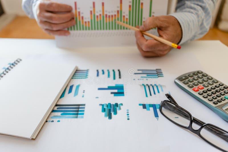Calcolatore, penna e vetri con i grafici finanziari fotografie stock libere da diritti