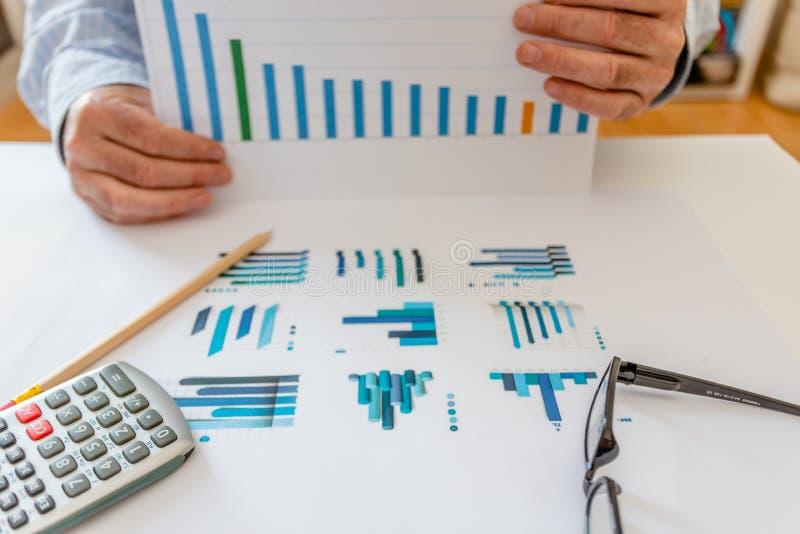 Calcolatore, penna e vetri con i grafici finanziari fotografia stock libera da diritti