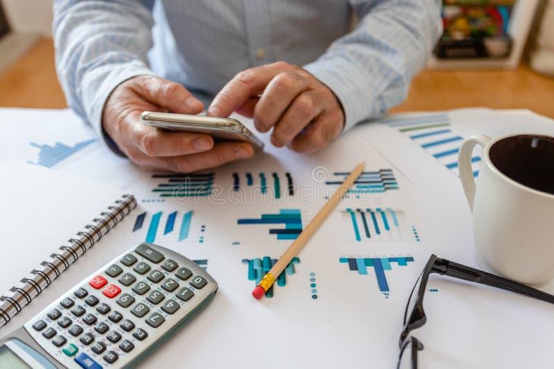 Calcolatore, penna e vetri con i grafici finanziari fotografie stock