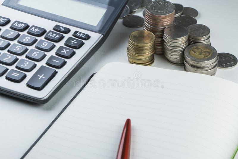 Calcolatore, penna rossa, pila tailandese della moneta e taccuino fotografie stock