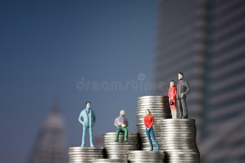 Calcoli l'uomo d'affari miniatura di piccoli investitore ed ufficio della gente immagini stock