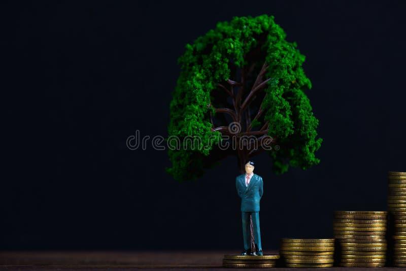 Calcoli l'uomo d'affari miniatura o il piccolo investitore della gente che sta la o immagine stock