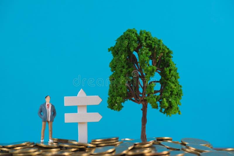 Calcoli l'uomo d'affari miniatura o il piccolo investitore della gente che sta la o fotografia stock