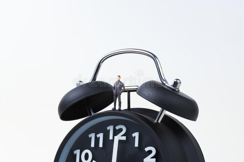 Calcoli l'uomo d'affari miniatura o la piccola gente che sta con l'allarme fotografie stock