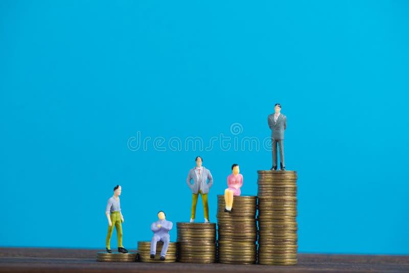 Calcoli l'uomo d'affari miniatura o piccoli investitore ed ufficio della gente fotografie stock