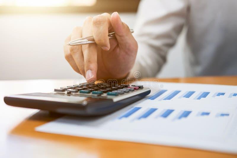 Calcoli maschii del ragioniere ed analizzare i dati finanziari del grafico immagine stock libera da diritti
