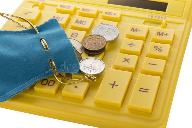 Calculadora amarilla con las monedas imagen de archivo