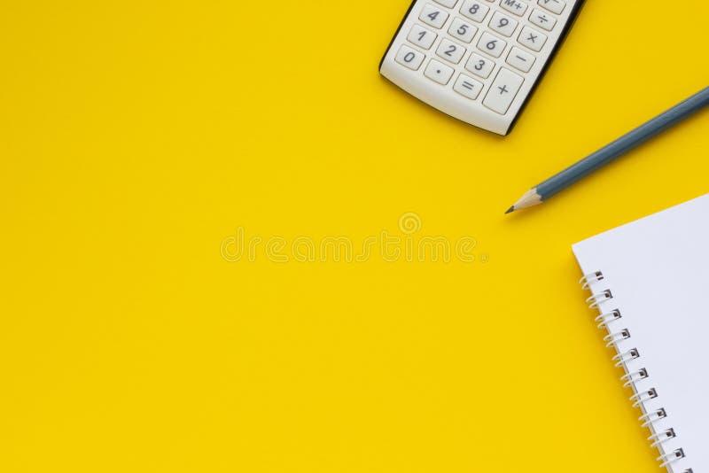 Calculadora, bloco de notas e lápis em um fundo amarelo, espaço para o texto imagem de stock