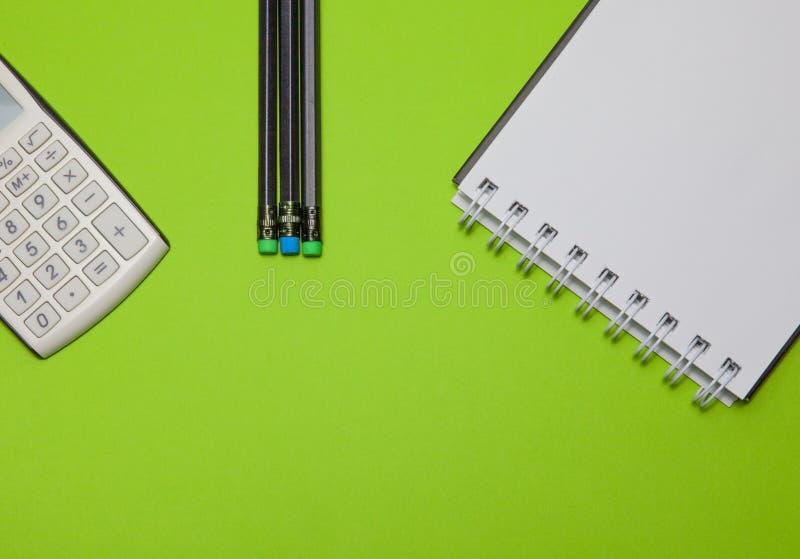 Calculadora, bloco de notas e lápis pretos em um fundo verde, vista superior foto de stock
