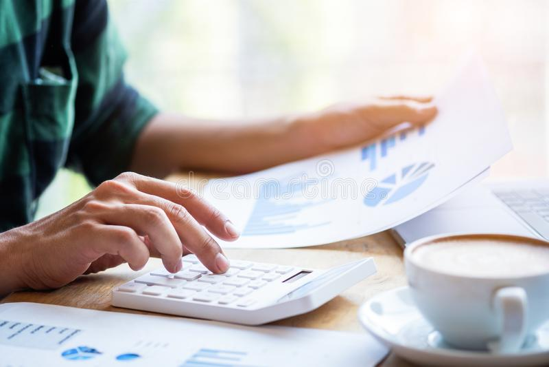 Calculadora a calcular, vida laboral moderna del uso del hombre, trabajando en espacio coworking, trabajo por la mañana con café, fotos de archivo libres de regalías