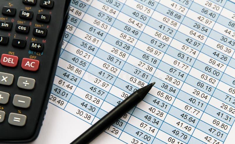 Calculadora científica e lápis preto sobre a tabela financeira da planilha com as colunas com números crescentes pela fileira fotos de stock