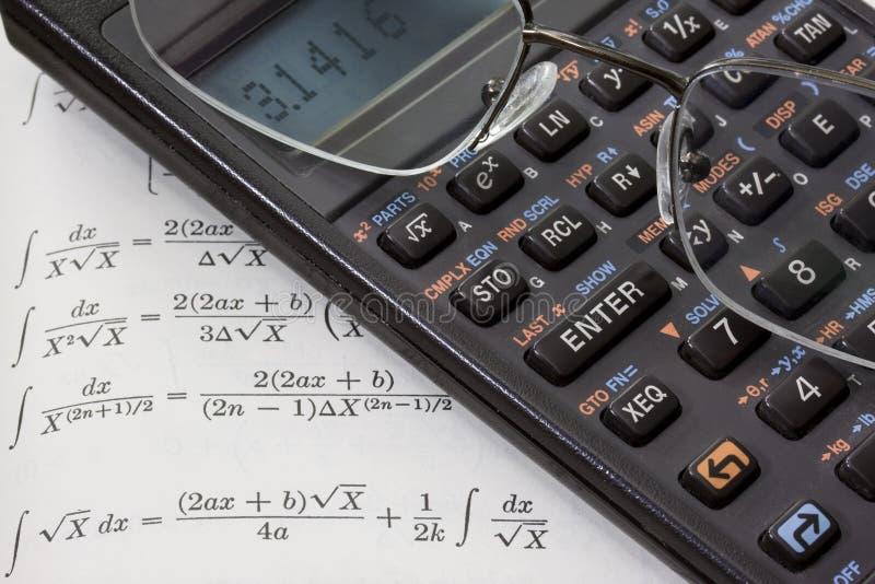 Calculadora científica, vidrios de lectura, libro de la matemáticas foto de archivo libre de regalías