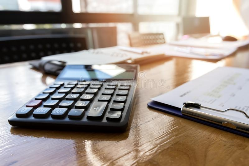 Calculadora con el papel del informe y materiales de oficina en el escritorio imagen de archivo