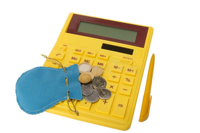Calculadora con las monedas y la cacerola fotografía de archivo