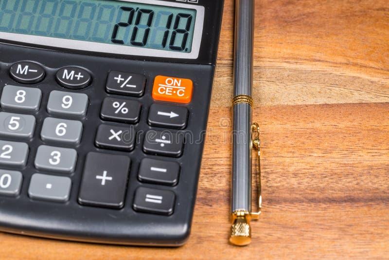 Calculadora con 2018 número y bolígrafo Pen Branch On Wooden Table Cierre para arriba fotografía de archivo libre de regalías
