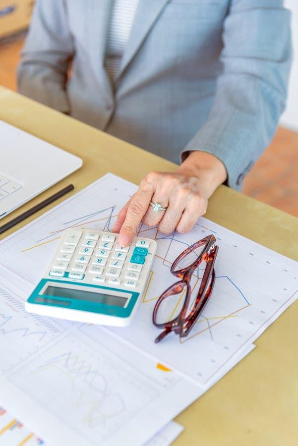 calculadora conmovedora mayor de la trabajadora con las lentes y el representante foto de archivo