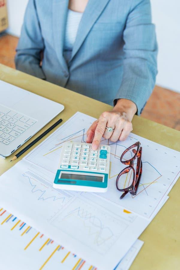 calculadora conmovedora mayor de la trabajadora con las lentes y el representante imágenes de archivo libres de regalías