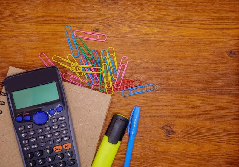 Calculadora da vista superior no caderno e nos artigos de papelaria no fundo de madeira marrom foto de stock