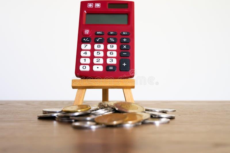 Calculadora de bolso vermelha atrás de uma pilha das moedas na tabela marrom do escritório fotos de stock