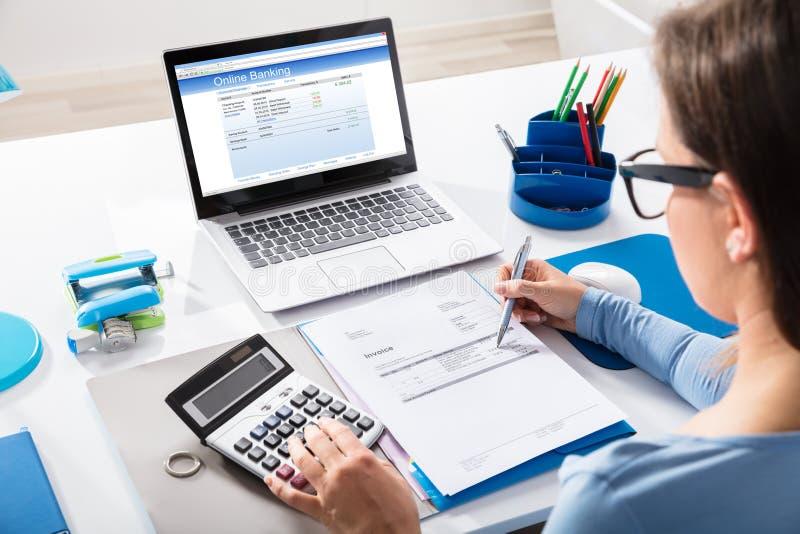 Calculadora de Calculating Invoice Using de la empresaria imagen de archivo libre de regalías
