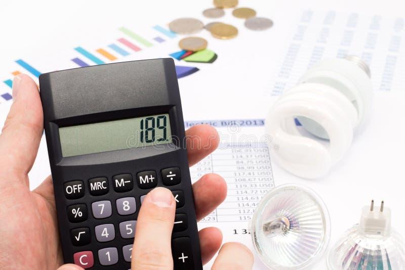 Calculadora do whit da ampola e euro- moedas foto de stock royalty free