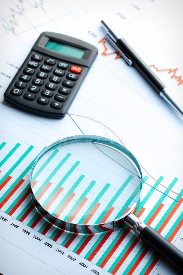 Calculadora e magnifier no gráfico de negócio. fotografia de stock royalty free