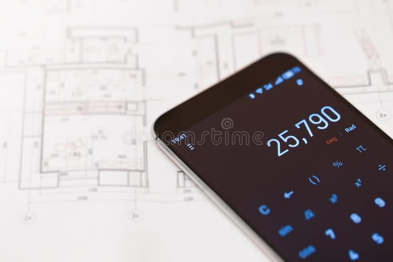 Calculadora en plan del smartphone y de las propiedades inmobiliarias imágenes de archivo libres de regalías