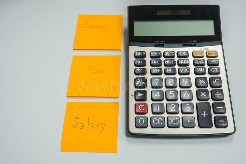 Calculadora isolada com a folha de papel do bônus, do imposto e do salário fotos de stock royalty free