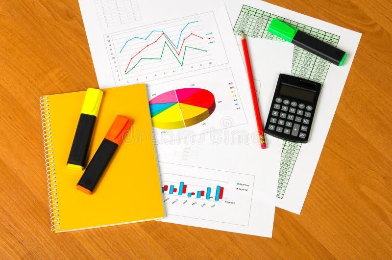 Calculadora, libreta, marcadores, hojas de papel con cuentas y fotos de archivo