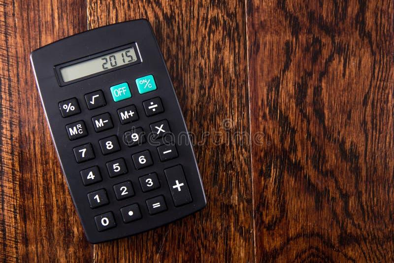 Calculadora negra en el escritorio de madera imagenes de archivo