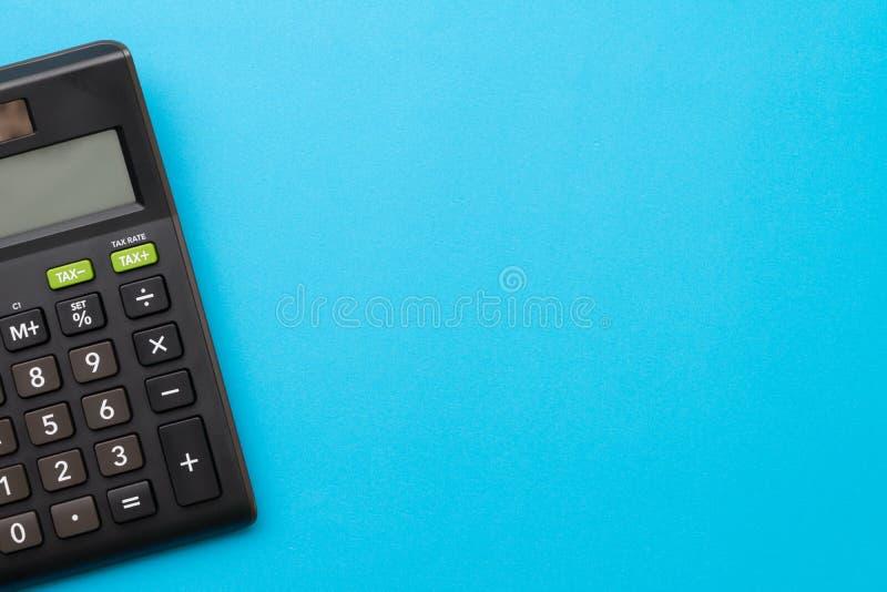Calculadora negra en fondo azul sólido con el espacio de la copia usando para la actividad, la contabilidad, el cálculo del impue fotos de archivo