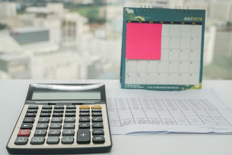 A calculadora para dados e a análise do orçamento com lembrete notam em julho de 2018 o calendário imagens de stock