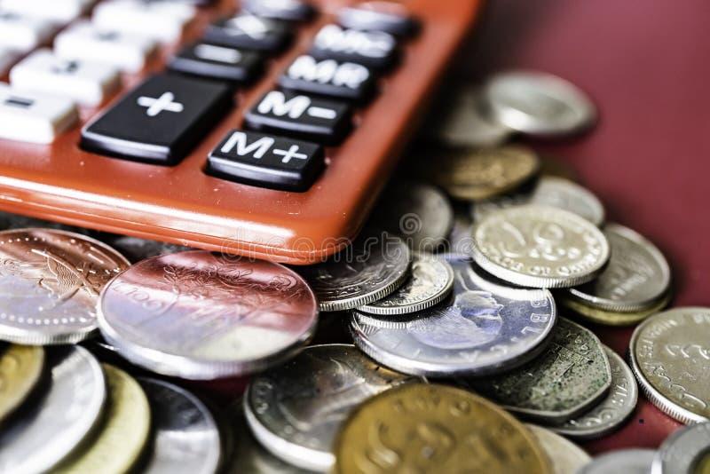 Calculadora vermelha do tampo da mesa com moedas de prata foto de stock