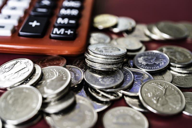 Calculadora vermelha do tampo da mesa com moedas de prata imagens de stock