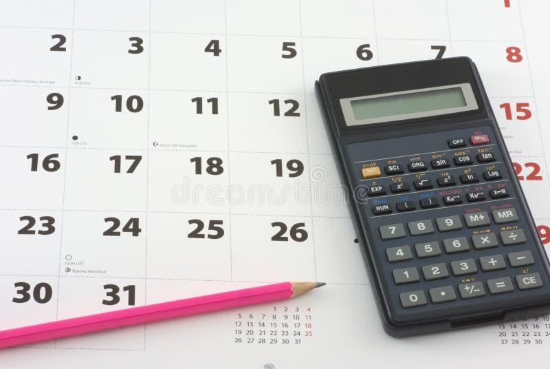 Calculadora y lápiz en el calendario imagen de archivo