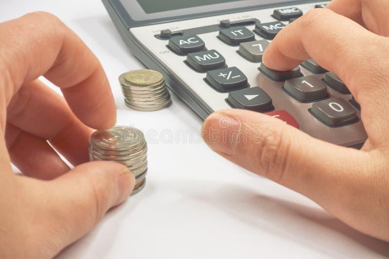 Calculadora y monedas del amontonamiento en columnas fotografía de archivo