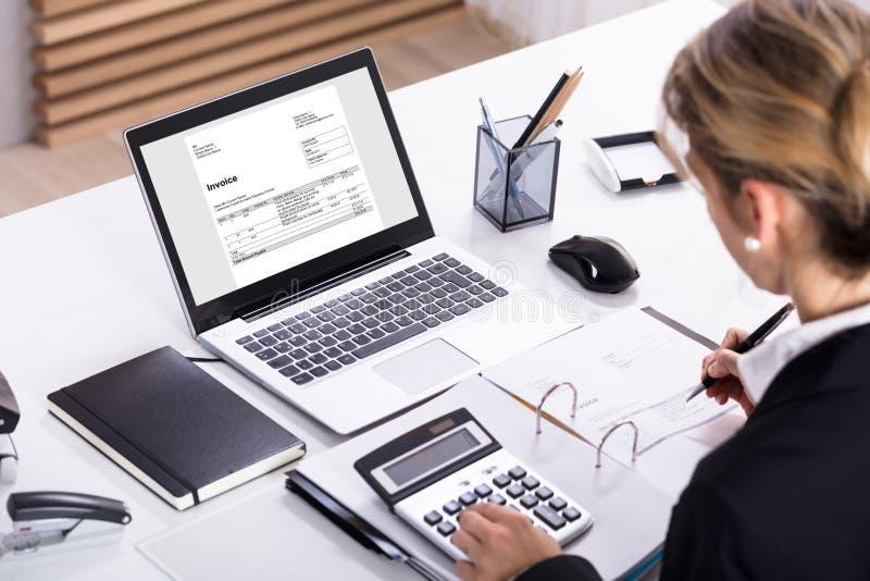 Calculadora y ordenador portátil de Calculating Invoice Using de la empresaria fotografía de archivo