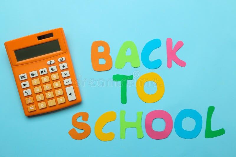 Calculadora y texto anaranjados de nuevo a escuela en un fondo de papel azul brillante Fuentes de oficina Educaci?n Visi?n superi foto de archivo libre de regalías